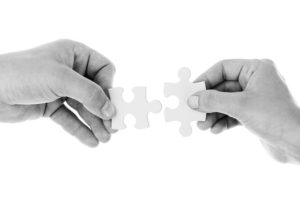 Photo of hands holding two jigsaw pieces
